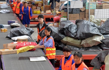 Workers sort parcels at express delivery company in China's Jiangxi